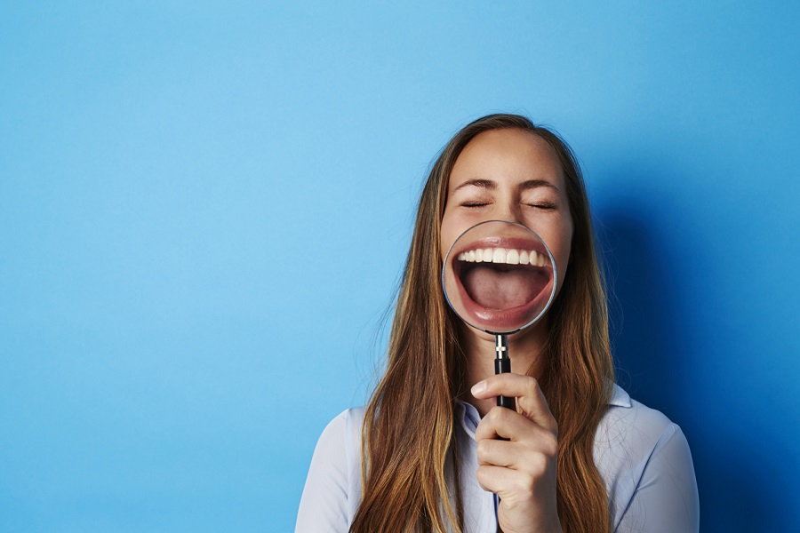 Beautiful woman laughing through magnifying glass