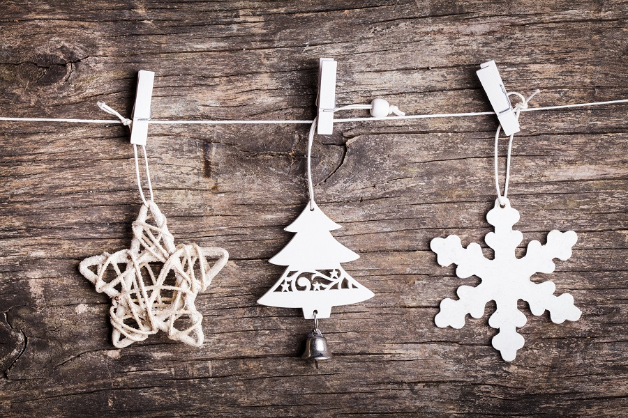 White christmas decorations attached to the rope, over wooden background