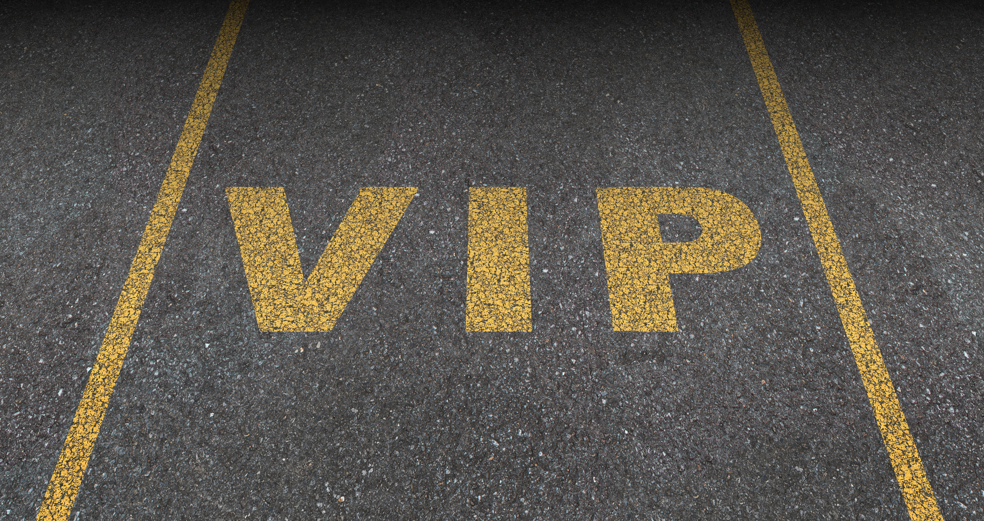VIP service symbol with a first class reserved parking space for with a sign painted on asphalt as a symbol of exclusive hospitality with the royal treatment with a blank area for text.