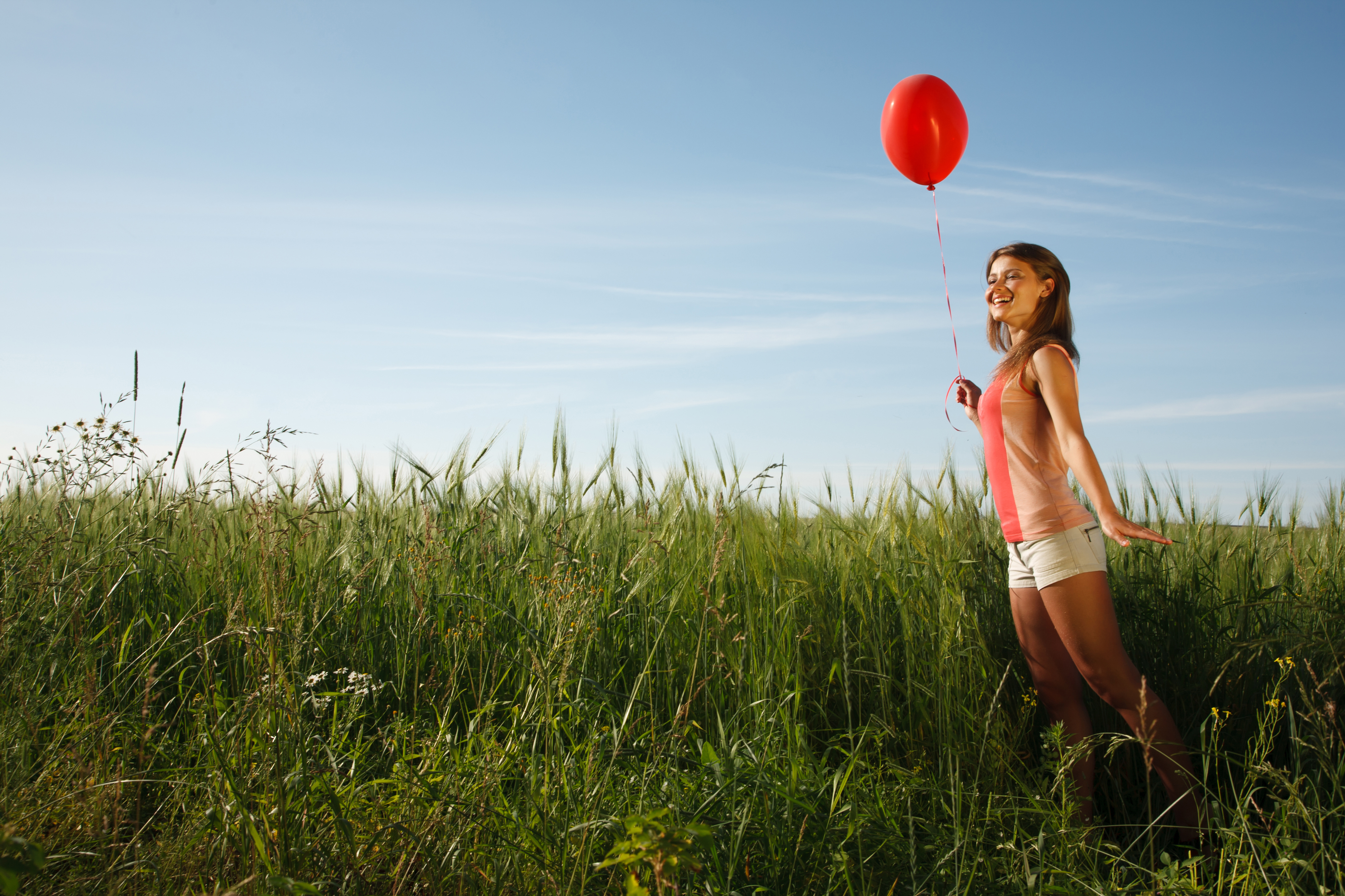 Girl with the red balloon stands on the field