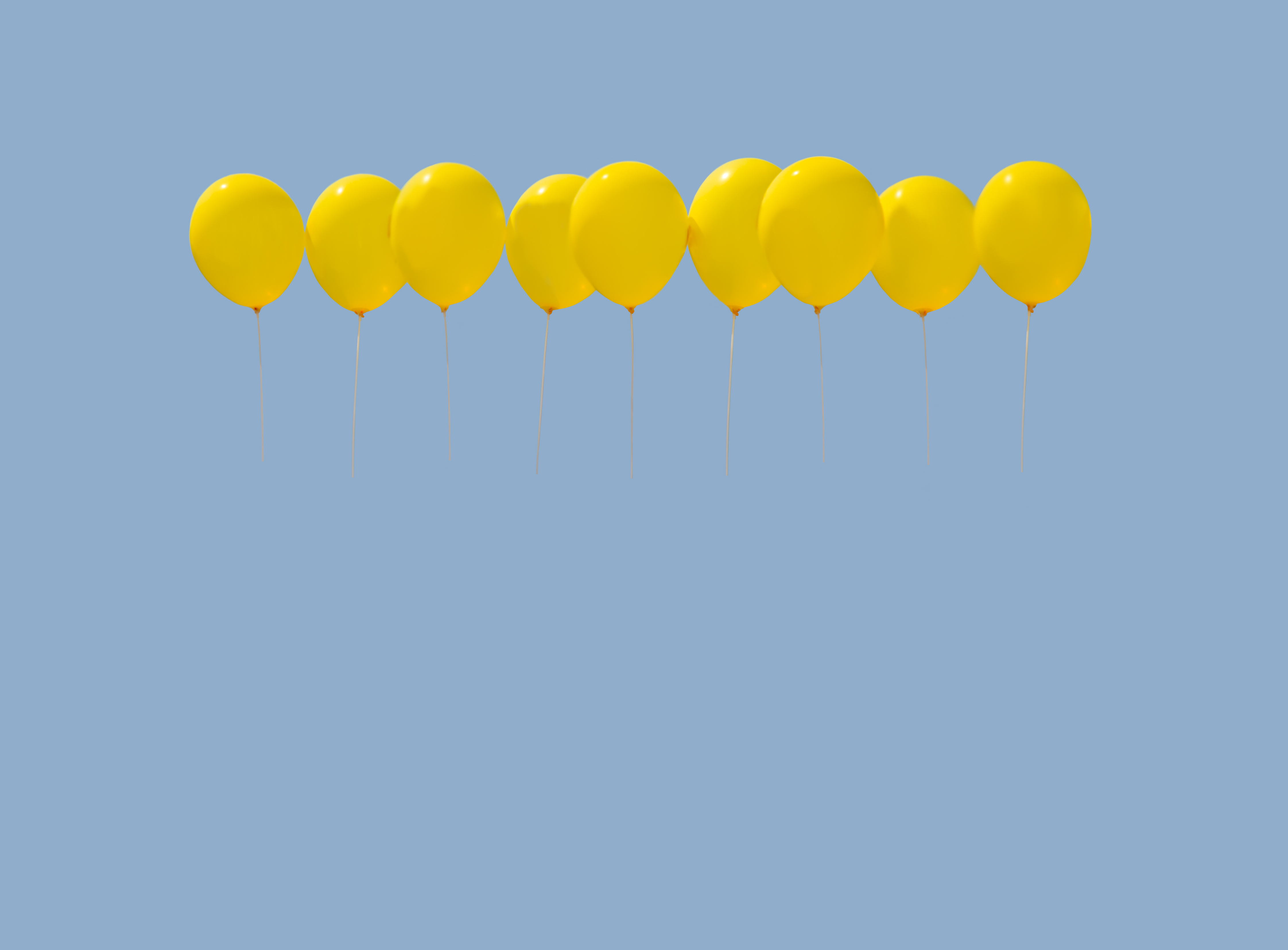 Nine yellow balloons soaring against light blue sky with copy space.